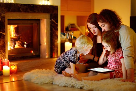 Happy young family using a tablet pc at home by a fireplace in warm and cozy living room on winter day