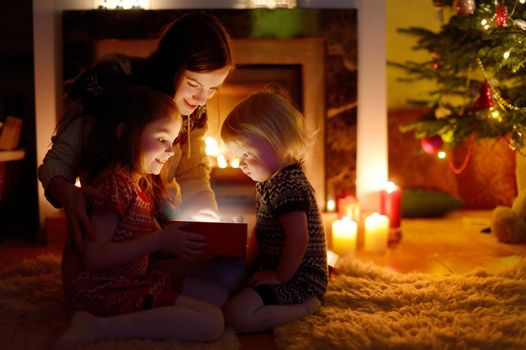 Young mother and her two little daughters opening a magical Christmas gift by a Christmas tree in cozy living room in winter