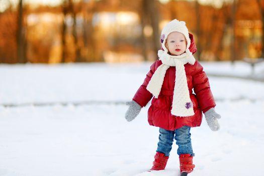 Adorable toddler girl having fun on beautiful winter day