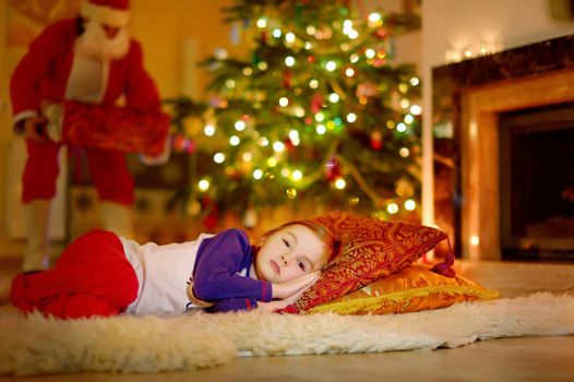 Adorable little girl sleeping under the Christmas tree by a fireplace on Christmas eve