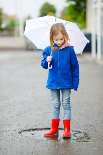 Adorable little girl holding white umbrella standing in a puddle on warm autumn day