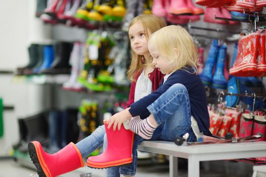 Two little sisters choosing and trying on new rain boots in a supermarket