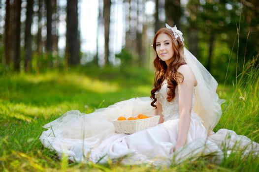 Young beautiful bride sitting on a grass in beautiful summer park