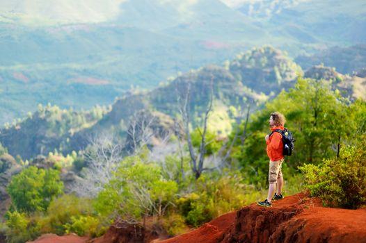 Young man enjoying stunning view into Waimea Canyon, Kauai, Hawaii