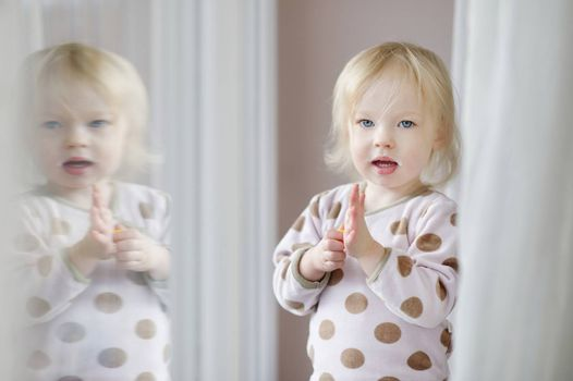 Adorable little girl with milk moustache standing by the window
