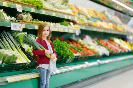 Little girl choosing a leek in a food store