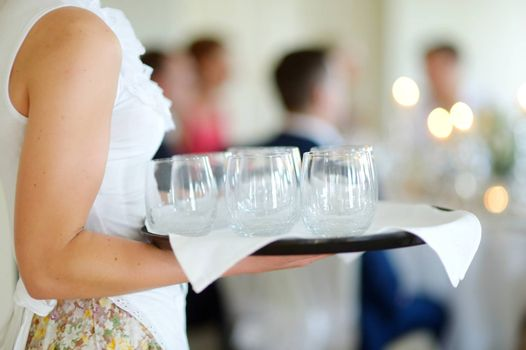 Waitress holding a dish of empty glasses