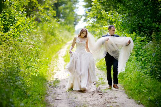 Young bride and groom walking in beautiful summer park