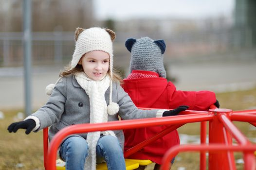 Two little sisters having fun on a playground on early spring