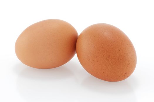 Two brown chicken eggs on a white background