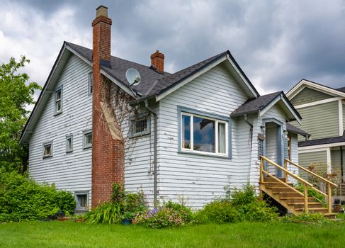 Old residential house with brick chimney and neglected lawn on the front