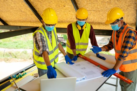 Construction workers and architect wearing protective mask to Protect Against Covid-19 are having discussion at construction site.