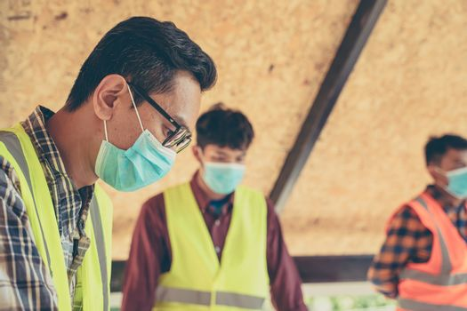 Group of engineering team wear protective face masks safety for Coronavirus Disease 2019 (COVID-19) meeting to plan for new project  measuring layout of building blueprints in construction site.