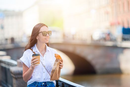 Woman with a croissant and coffee outdoors on the promenade