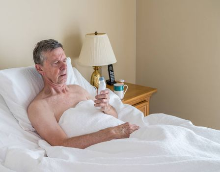 Single caucasian senior man in inclined bed taking temperature with thermometer