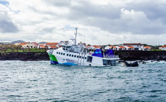 """MADALENA, AZORES, PORTUGAL - MARCH 02, 2018: The ferry """"Mestre Simao"""" remains partly submerged at the port entrance after it ran aground two months earlier."""