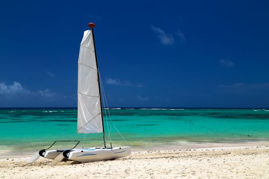 Catamaran on the exotic coast of the Atlantic Ocean with a background from golden sand of emerald water and the blue sky. Beautiful Carribean sea, panoramic view from the beach. Picture with copy space.