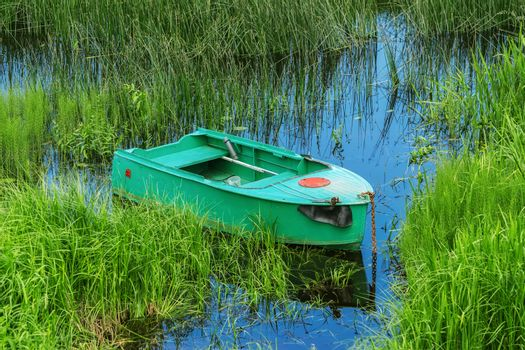 Old metal rowboat moored on the lake