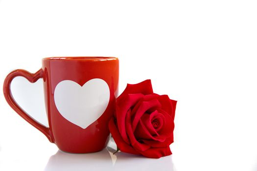 Closeup of an orange coffee mug with a beautiful blooming red rose on white backbround.  Valentine's,  anniversary, wedding concept.