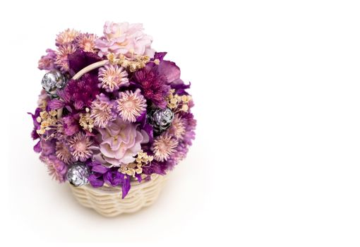 A basket of dried wild flowers on white background. Macro image.