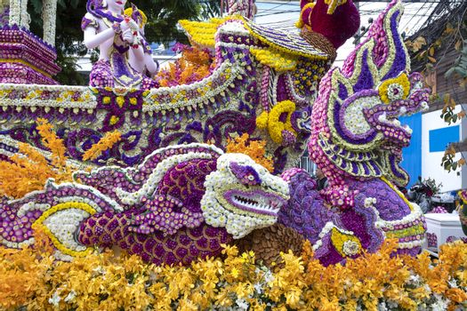 A colorful floral float depicting angels and mythical animals in an annual flower festival parade in Chiang mai, Thailand.