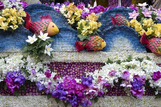 A colorful floral float depicting ocean waves and tropical fish in an annual flower festival parade in Chiang mai, Thailand.