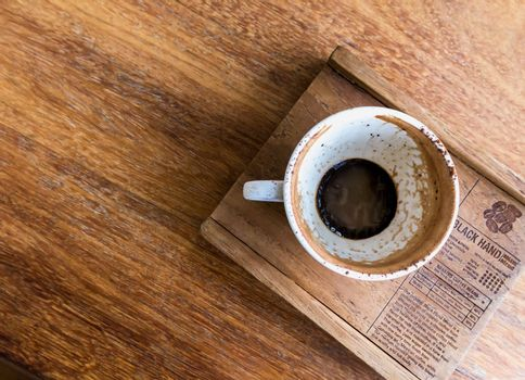 Empty coffee cup and a wooden tray on the wood table at coffee shop.view from above
