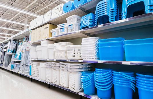 Plastic baskets,Containers and plastic chairs on shelves at grocery store supermarket.Plastic household section in Hypermarket.