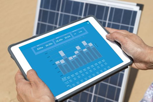 Woman hands on electronic tablet controlling solar panel with an app (blue screen with statistics and graph of the energy production & consumption)