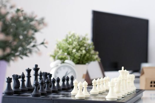 Chess board. Business concept. Business Strategy. Work table with chess board games. Win Competition with good strategy. White Alarm clock and computer on work desk. Data financial analysis.