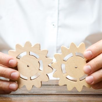 Businessman in white shirt connects two wooden gears. Improving work efficiency, establishing new connections and suppliers. Symbolism of establishing business processes and communication.