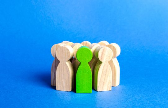 Green figurine of a person in a crowd. Society, social group. management of people. Leadership qualities, talented and enterprising employee. HR is looking for new employees, choice among candidates