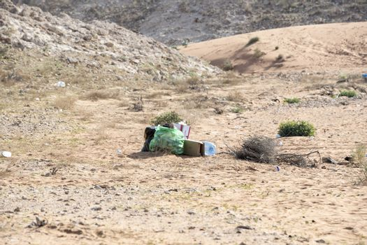 Garbage left in Desert (plastic bag, plastic bottles, cartoons and other detritus). Plastic pollution and environmental issue