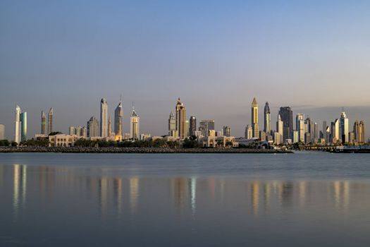 Scenic Dubai Downtown Skyline at sunset with copy space in the sky and in the sea, United Arab Emirates (UAE), Middle East