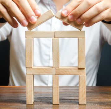 A man completes a building of dominoes. Expansion and development. Creating a business, startup. company protection, support for small and medium-sized businesses. Insurance assistance