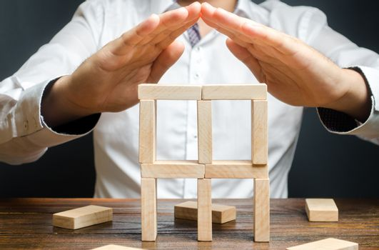 A man holds his hands in the symbol of the roof over the building of dominoes. Creating a business, startup. company protection, support for small and medium-sized businesses. Insurance assistance