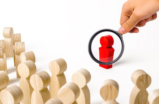 A magnifying glass looks at a red figurine of a man near a crowd. Leader, leadership and initiator of action. work or business organization. team building. Idol and example to follow. Distrust