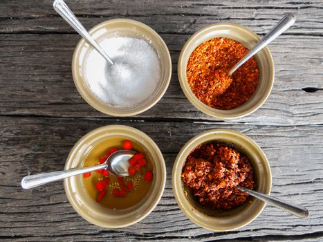 food flavoring concept. sugar , cayenne pepper, vinegar and chili paste in small bowl for food flavoring on wooden table background