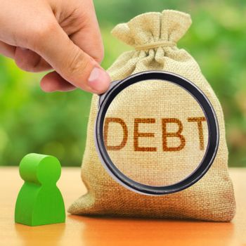 A magnifying glass looks at a bag with the inscription DEBT. Unclosed obligations between two persons, financial or moral debt. refusal to return debts. restructuring