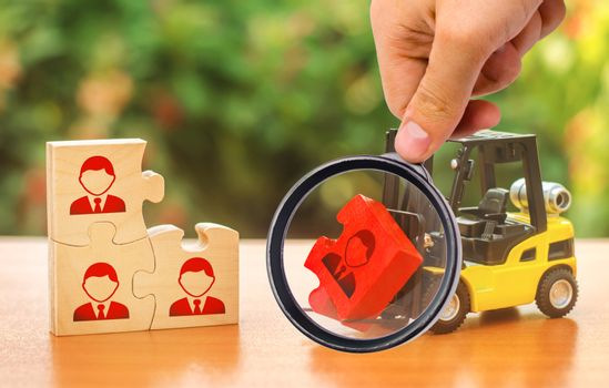 A magnifying glass looks at a forklift truck carries a red puzzle to the unfinished assembly of business team. Search, recruitment staff, hiring leader. Creating efficient and productive business unit