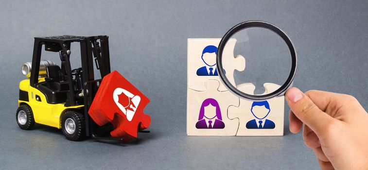 A magnifying glass looks at a red puzzle to the unfinished assembly of business team. Search, recruitment staff, hiring leader. Creating an efficient and productive business unit. Leadership