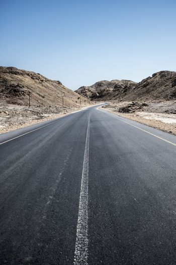 An empty tarmac road going thru arid mountains in the Sultanate of Oman in the Al Wusta Governate