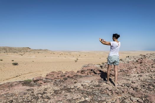 Woman tourist taking a picture with her smartphone of a valley in the Al Wusta Governate in the Sultanate of Oman