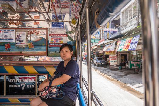 Bangkok, Thailand - June 10, 2017 : Asia women 40s white skin prepare a fare on a minibus car for a passenger travel in city to destination