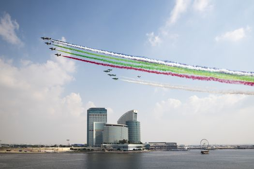 Emiratis Air Patrol flying above Festival City for the 46th National Day with UAE colors vapor trails, Dubai, United Arab Emirates