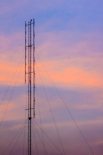 Cellular transmitter, folded dipole radio antenna for telecommunications with colorful sky background. Silhouette amateur radio antenna tower in dramatic sky background.