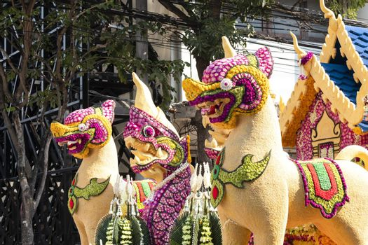 Details of mystical creatures decorated with fresh flowers on a float used in the February Flower Festival Parades in the City of Chiangmai, Thailand.