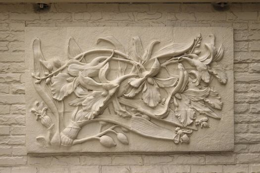 Beautiful white Java stucco patterned on the boundary wall. Vintage white wall bas-relief stucco in plaster, depicts Lotus flowers background.