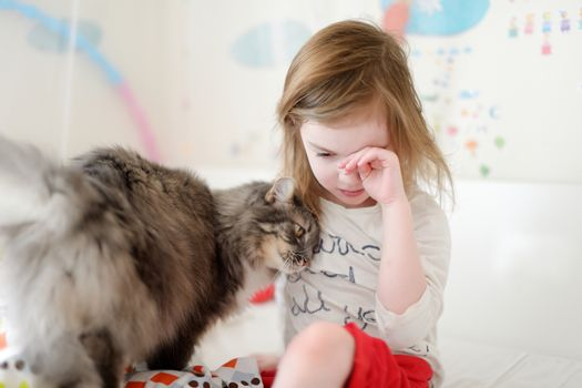 Little preschooler girl in pajamas and her cat on sunny morning