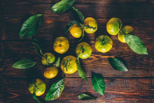 Yellow-green tangerines with leaves over wooden surface. View from above.
